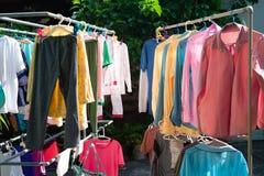 Färgrik våt kläder som hänger på stålklädstrecket för att torka vid värmen av solen arkivfoton
