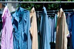 Färgrik våt kläder som hänger på stålklädstrecket för att torka vid värmen av solen royaltyfri foto