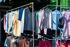 Färgrik våt kläder som hänger på stålklädstrecket för att torka vid värmen av solen arkivbild