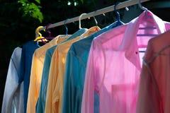Färgrik våt kläder som hänger på stålklädstrecket för att torka vid värmen av solen royaltyfria foton