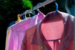 Färgrik våt kläder som hänger på stålklädstrecket för att torka vid värmen av solen royaltyfri fotografi