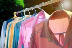 Färgrik våt kläder som hänger på stålklädstrecket för att torka vid värmen av solen arkivbilder