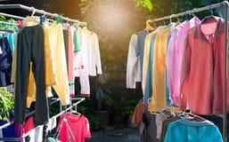 Färgrik våt kläder som hänger på stålklädstrecket för att torka vid värmen av solen arkivfoto