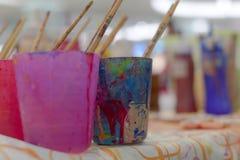 Färgrik vattenfärgutrustning liksom paintbrushsexponeringsglas och färgmagasinet är tillgängliga för barn fotografering för bildbyråer