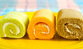 Färgrik vibrerande rullkaka på gult mjuk och suddighetsbegrepp för platta, Arkivbilder