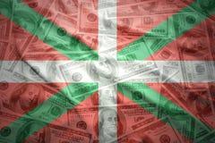 Färgrik vinkande basque landsflagga på en dollarpengarbakgrund Royaltyfri Bild