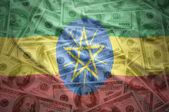 Färgrik vinkande ethiopian flagga på en dollarpengarbakgrund Royaltyfri Fotografi