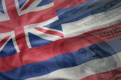 Färgrik vinkande flagga av den hawaii staten på en amerikansk dollarpengarbakgrund Arkivfoton