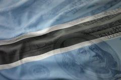 Färgrik vinkande nationsflagga av Botswana på en amerikansk dollarpengarbakgrund Arkivbilder