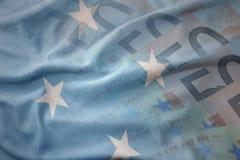Färgrik vinkande nationsflagga av Federated States of Micronesia på en bakgrund för europengarsedlar royaltyfria bilder