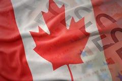 Färgrik vinkande nationsflagga av Kanada på en bakgrund för europengarsedlar Royaltyfri Bild