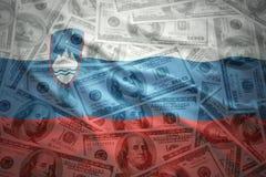Färgrik vinkande slovenian flagga på en dollarpengarbakgrund Arkivbilder