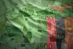 Färgrik vinkande zambisk flagga på en eurobakgrund Arkivfoton