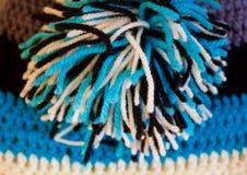 Färgrik virkninghatt med pomponen Royaltyfri Fotografi