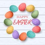 Färgrika ägg för påsk med olika enkla prydnader i cirkelram vitt trä för bakgrund Arkivbild