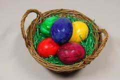 Färgrika ägg i en korg Arkivfoto