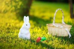 Färgrika ägg och den gulliga vita leksakkaninen under ägget jagar på påsk Royaltyfri Fotografi