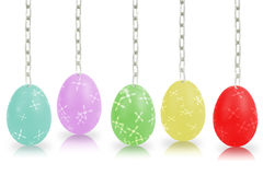 Färgrika ägg som hänger vid kedjor på den vita bakgrunden Arkivfoto