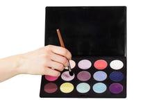 Färgrika ögonskuggor för palett, kosmetisk borste i den isolerade kvinnliga handen Royaltyfria Bilder