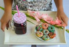 Färgrika amerikanska donuts och ny körsbärsröd fruktsaft tjänade som för frukost Royaltyfri Fotografi