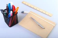 Färgrika anteckningsböcker och kontorstillförsel på den vita tabellen Royaltyfri Bild