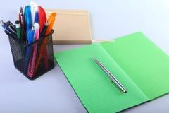 Färgrika anteckningsböcker och kontorstillförsel på den vita tabellen Arkivfoto