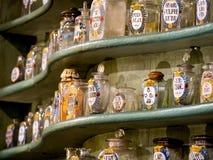Färgrika antika flaskor på trähylla Arkivbilder