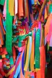 Färgrika bönband som binds till önskaträdet Arkivfoto