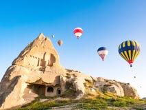 Färgrika ballonger för varm luft som över flyger, vaggar landskap på Cappadoc arkivfoton