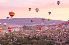 Färgrika ballonger för varm luft som över flyger, vaggar landskap på Cappadoc arkivbilder
