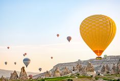Färgrika ballonger för varm luft som över flyger, vaggar landskap på Cappadocia Turkiet royaltyfria foton