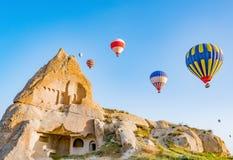 Färgrika ballonger för varm luft som över flyger, vaggar landskap på Cappadocia Turkiet arkivfoto