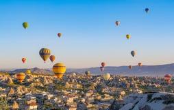 Färgrika ballonger för varm luft som över flyger, vaggar landskap på Cappadocia Turkiet royaltyfri foto