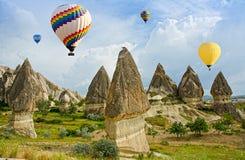Färgrika ballonger för varm luft som flyger över vulkaniska klippor på Cappadocia royaltyfria bilder