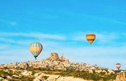 Färgrika ballonger för varm luft som flyger nära Uchisar, rockerar på soluppgång, Cappadocia, Turkiet royaltyfri fotografi