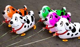 Färgrika ballonger i form av hundkapplöpning Arkivfoton