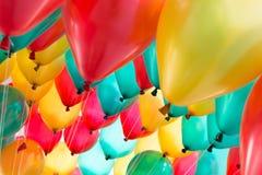 Färgrika ballonger med det lyckliga berömpartiet Arkivfoton