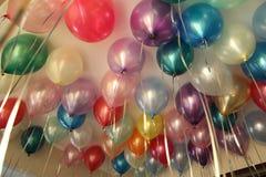 Färgrika ballonger, ballonger med helium, under taket, födelsedag, ferie arkivbilder