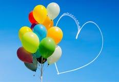 Färgrika ballonger och hjärta som är skriftliga i himlen med flygplan Arkivbilder