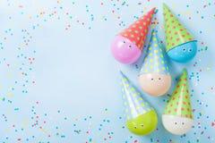Färgrika ballonger och konfettier på blå bästa sikt för tabell det vidfästa kortet för bakgrundsfödelsedagasken många egna deltag Royaltyfri Foto