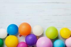 Färgrika ballonger på blå träbästa sikt för tabell det vidfästa kortet för bakgrundsfödelsedagasken många egna deltagaremöjlighet Royaltyfria Foton