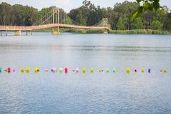 Färgrika ballonger på vatten- och klaffbrobakgrund Arkivfoto