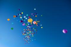 Färgrika ballonger som flyger i himmelpartiet Arkivbild