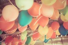 Färgrika ballonger som svävar på taket av ett parti i tappning Fotografering för Bildbyråer