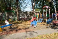 Färgrika barnlekplatsaktiviteter parkerar offentligt i solig dag Höst Tända och skuggar Arkivbild