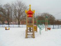 Färgrika barns glidbana i snön parkerar område av ‹för †staden Royaltyfria Bilder
