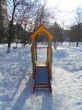 Färgrika barns glidbana i snön parkerar område av ‹för †staden Royaltyfri Foto