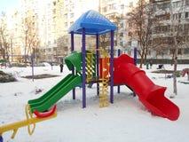 Färgrika barns glidbana i snön parkerar område av ‹för †staden Arkivfoto