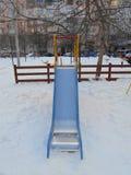 Färgrika barns glidbana i snön parkerar område av ‹för †staden Arkivfoton