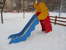 Färgrika barns glidbana i snön parkerar område av ‹för †staden Fotografering för Bildbyråer